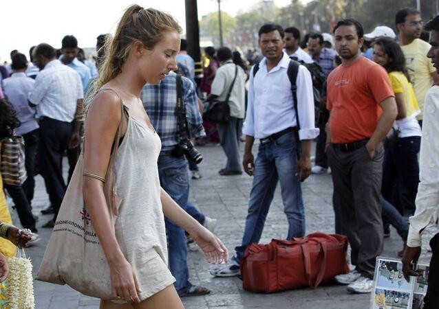 In this Tuesday, April 2, 2013 photo, German tourist Carolina De Paola, 22, walks near the landmark Gateway of India in Mumbai, India