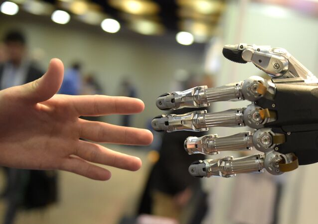 A man moves his hand toward SVH (Servo Electric 5 Finger Gripping Hand) automated hand made by Schunk during the 2014 IEEE-RAS International Conference on Humanoid Robots in Madrid on November 19, 2014