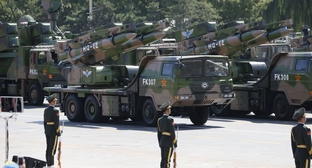 Military vehicles carry HQ-12 surface-to-air missile batteries during a parade commemorating the 70th anniversary of Japan's surrender during World War II.