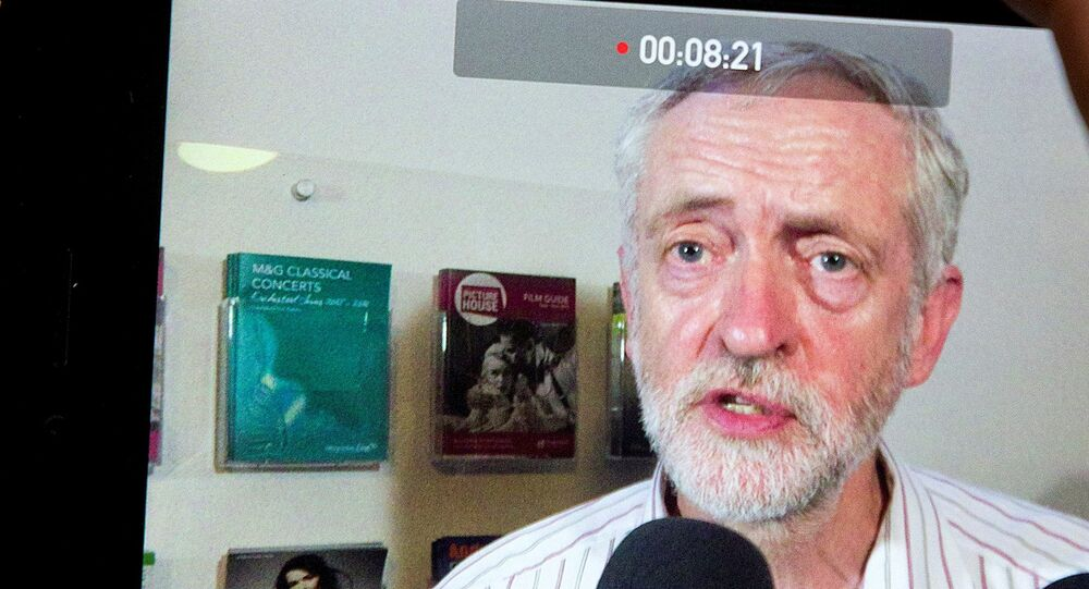 A journalist records British Labour Party leader Jeremy Corbyn on a mobile phone.