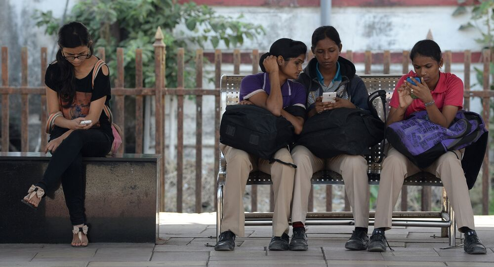 Indian women check their mobile telephones at a free Wi-Fi Internet zone in Mumbai (File)