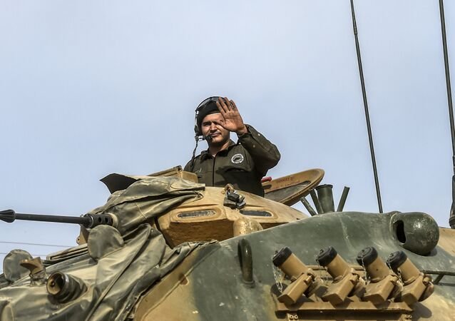 This picture taken around 5 kilometres west from the Turkish Syrian border city of Karkamis in the southern region of Gaziantep, on August 25, 2016 shows a soldier gesturing as Turkish Army tanks drive to the Syrian Turkish border town of Jarabulus
