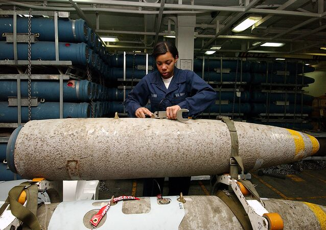 An aviation ordnance technician handling the bomb body of a thermally protected (insulated to slow cook-off time in case of fire) Mark 84 aboard the USS George Washington.