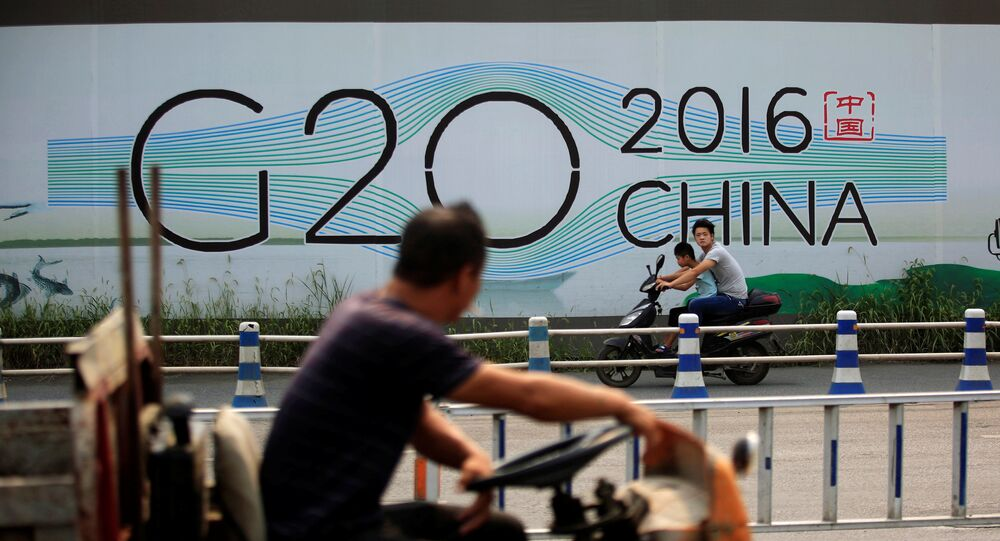 People cycle past a billboard for the upcoming G20 summit in Hangzhou, Zhejiang province, China, July 29, 2016