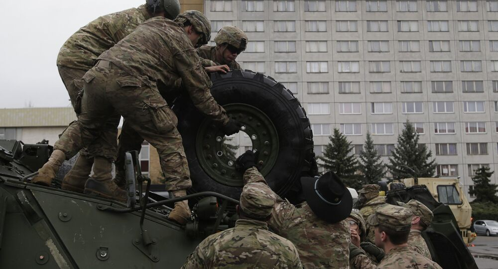 US army soldiers roll a tyre from top of a stryker armored vehicle during a stop of his convoy in Prague, Czech Republic, Tuesday, March 31, 2015