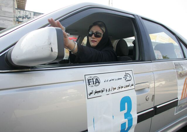 An Iranian driver adjusts her side mirror at the start of the women's rally in the northern Iranian city of Chalus 05 September 2007