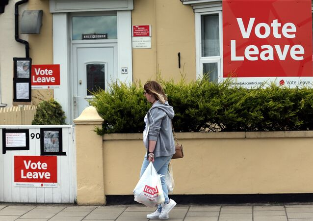 A woman walks past a house where Vote Leave boards are displayed in Redcar, north east England on June 27, 2016.