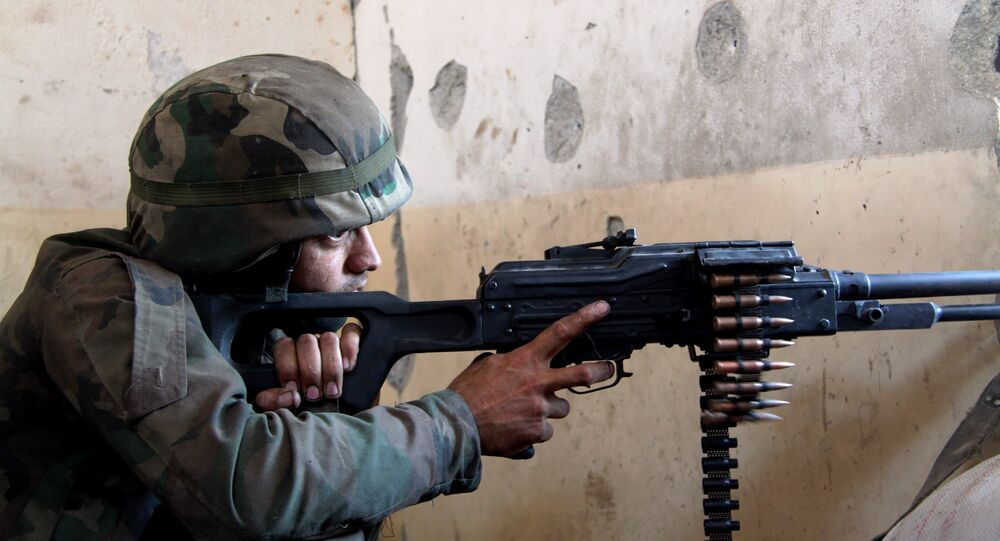 A Syrian army fighter in position during the assault of the BBC school in the southern part of the Syrian city of Aleppo