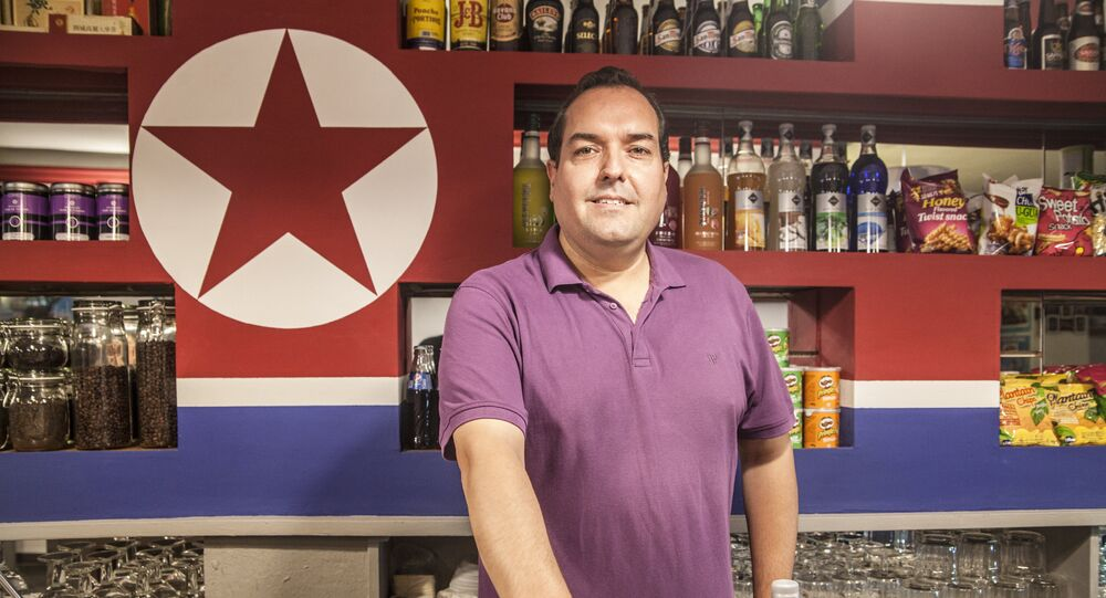 Alejandro Cao de Benós poses in Café Pyongyang with North Koeran flag on the background