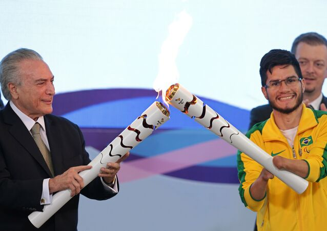 Brazil's acting President Michel Temer, left, lights the torch of Paralympic athlete Yohansson Nascimento during a ceremony for 2016 Rio Paralympic Games at the Planalto Presidential Palace, in Brasilia, Brazil, Thursday, Aug. 25, 2016.