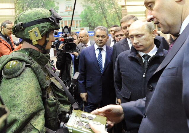 Russian President Vladimir Putin, second left, reviews examples of 'Ratnik' modern military garment during a working visit to OJSC 'Kalashnikov Concern' in Izhevsk. Center - Russian Denfence Minister Sergei Shoigu.