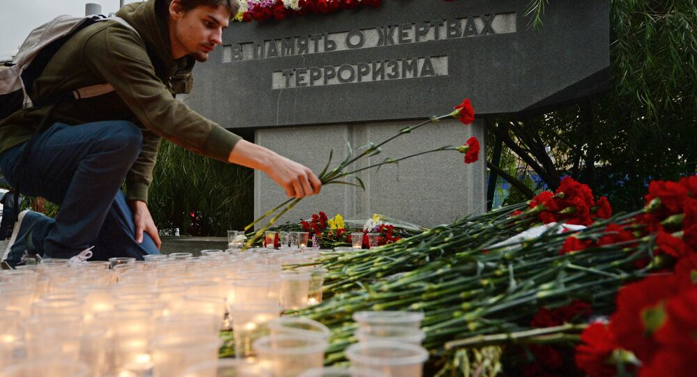 A 'Young Guard' movement activist is laying flowers to memorial to victims of terrorist attack on the Dubrovka Theater Center in Moscow
