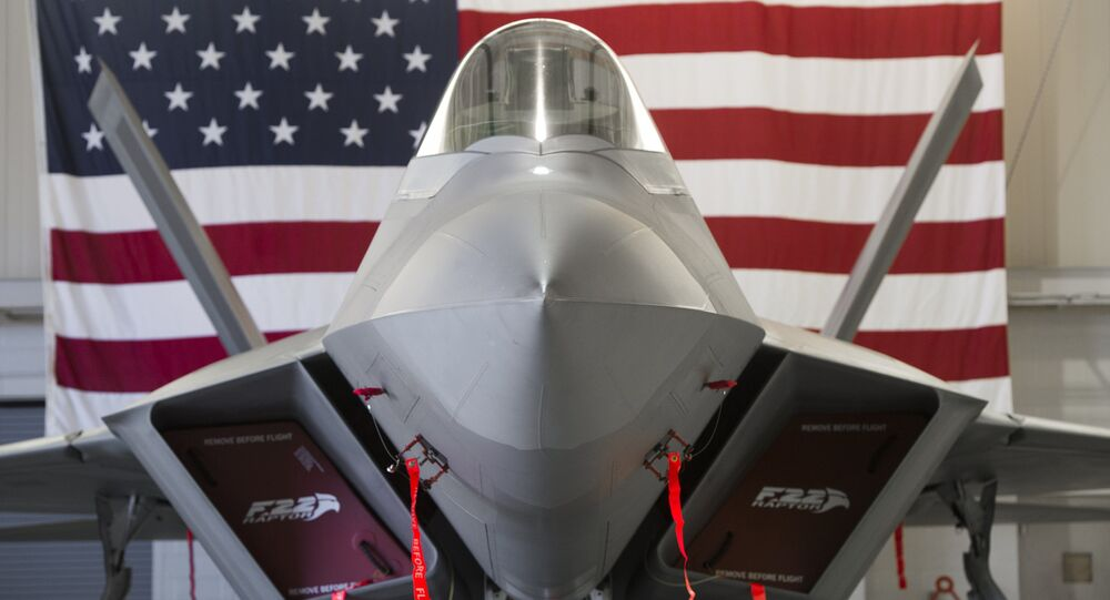 A US Air Force Lockheed Martin F-22 Raptor stealth fighter aircraft is parked inside a hangar