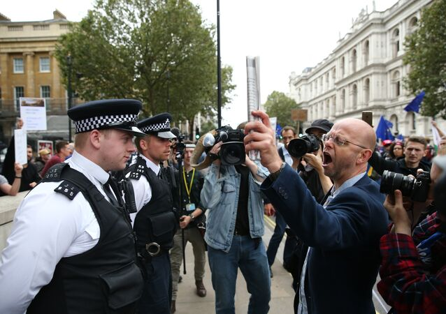 Police stand in a cordon as a pro-Europe (R) marcher on a March for Europe demonstration against the Brexit vote in Parliament Square in central London