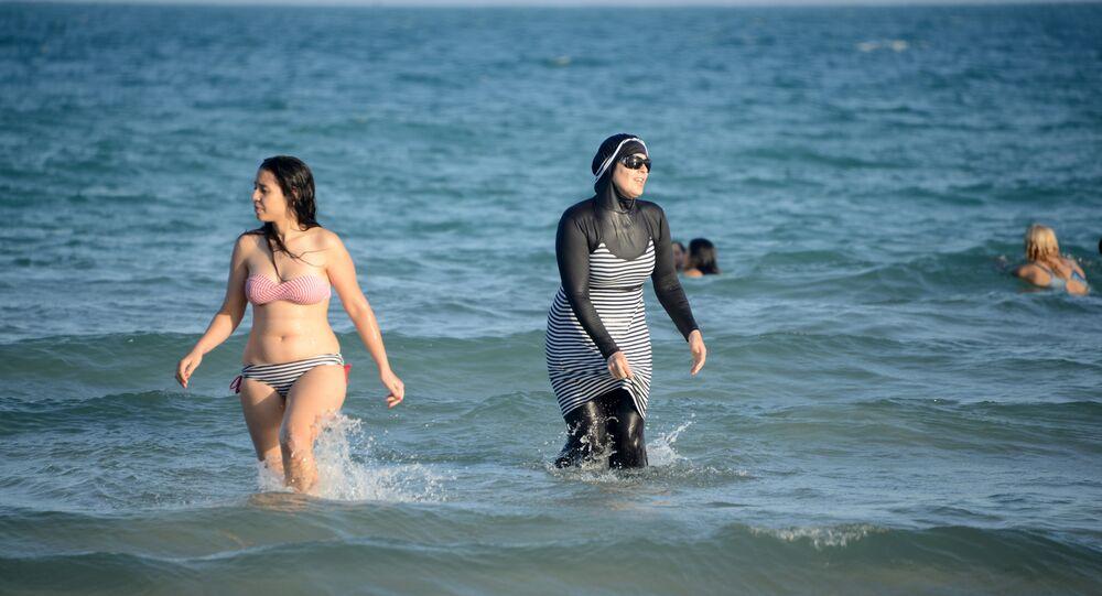 Tunisian women, one (R) wearing a burkini, a full-body swimsuit designed for Muslim women, swim at Ghar El Melh beach near Bizerte, north-east of the capital Tunis