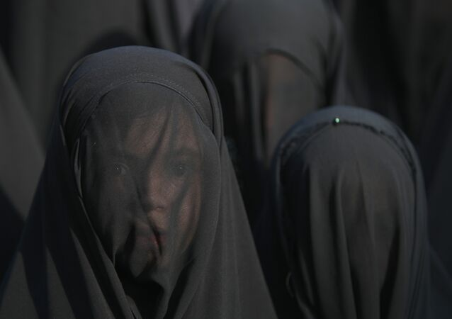 An Iraqi Shiite girl, whose face is covered with a veil, takes part in a parade in preparation for the peak of the mourning period of Ashura in Baghdad's northern district of Kadhimiya on October 22, 2015 (File photo).