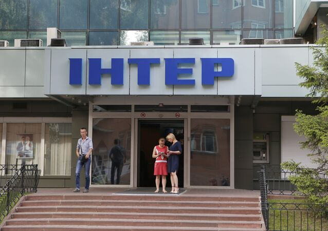 People walk out off of Inter TV channel in Kiev, Ukraine,Tuesday, May 26, 2015