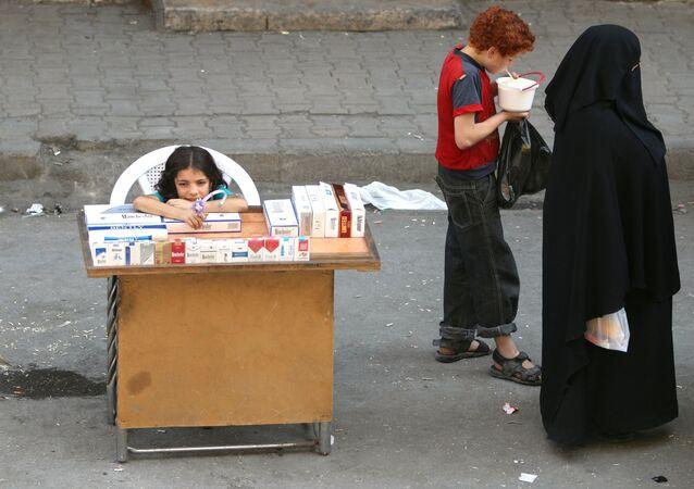 A boy eats yogurt near a girl selling cigarettes in the rebel held al-Shaar neighborhood of Aleppo, Syria, August 30, 2016.