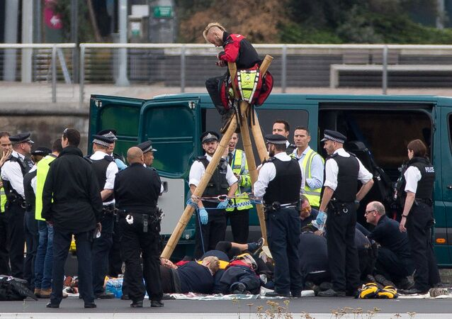 Emergency services surround protestors from the movement Black Lives Matter after they locked themselves to a tripod on the runway at London City Airport in London on September 6, 2016