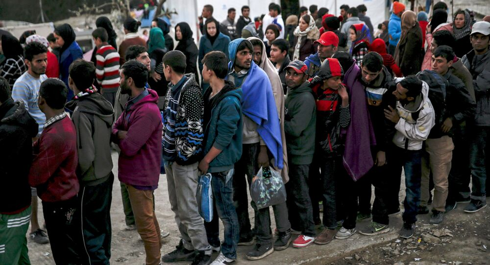Refugees and migrants line up for a food distribution at the Moria refugee camp on the Greek island of Lesbos, November 5, 2015