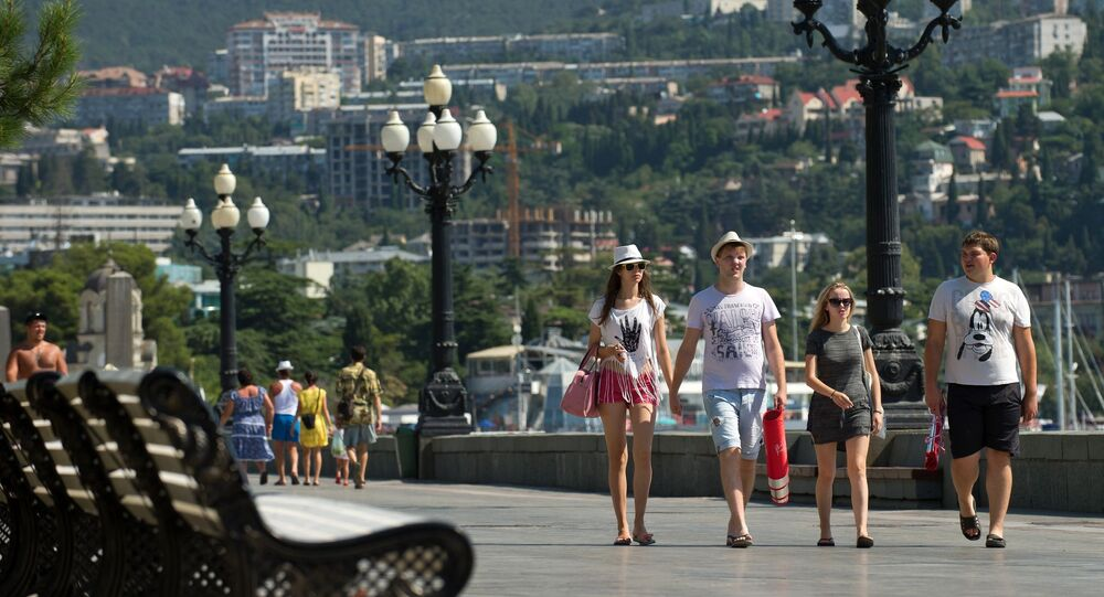Holiday-makers walk on the waterfront in downtown Yalta.