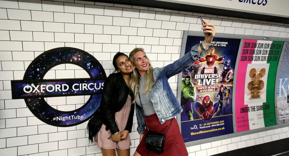 Passengers pose for a selfie as they wait for the Night Tube train service at Oxford Circus on the London underground system in London, Britain August 20, 2016.