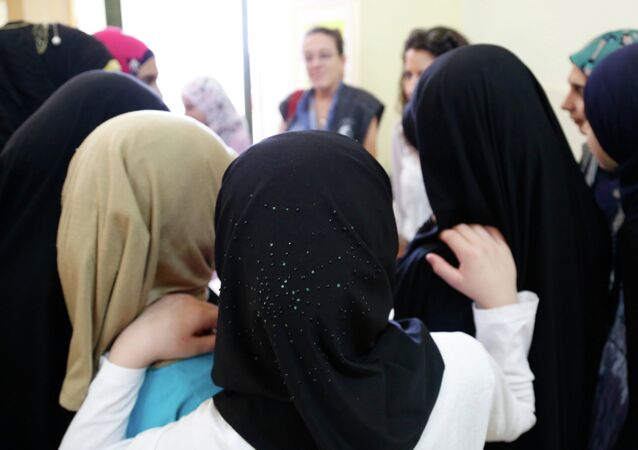 Syrian and Lebanese girls huddle round in a group discussion about early marriage at a community centre in southern Lebanon.