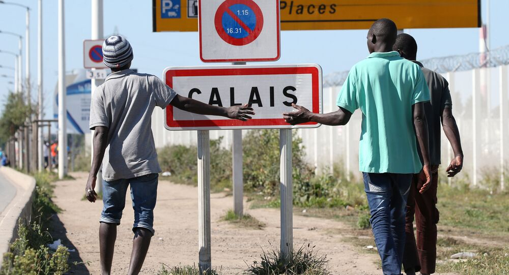 Migrants pass by a road sign as they leave the northern area of the camp called the Jungle in Calais, France, September 7, 2016