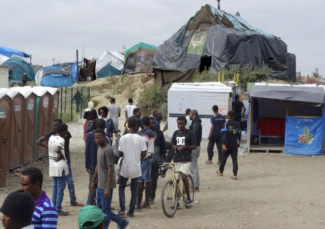 Migrants walk in the northern area of the camp called the Jungle in Calais, France, September 6, 2016