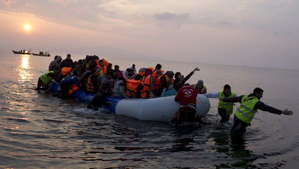 In this Sunday, March 20, 2016 file photo, volunteers help migrants and refugees on a dingy as they arrive at the shore of the northeastern Greek island of Lesbos, after crossing the Aegean sea from Turkey. - Sputnik International