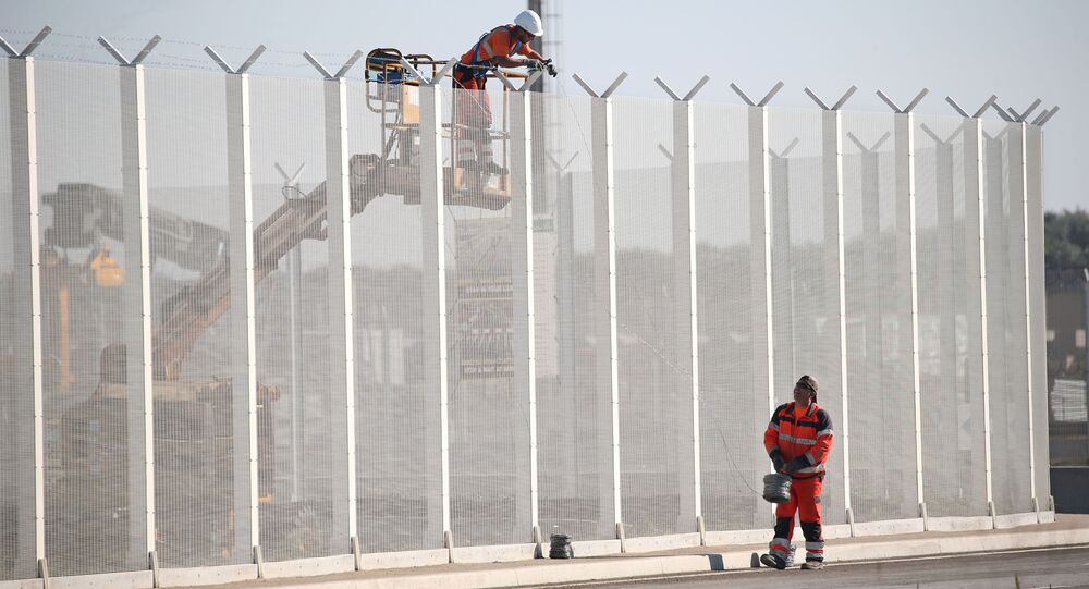 Workers set-up barbed wires on top of a fence along the harbour of Calais to prevent migrants jumping aboard lorries, France, September 7, 2016