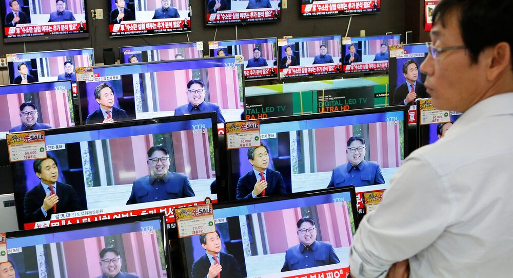 A sales assistant watches TV sets broadcasting a news report on North Korea's fifth nuclear test, in Seoul, South Korea, September 9, 2016.