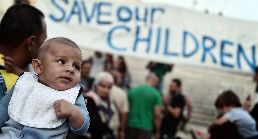 This file photo taken on September 02, 2016 shows refugees with their children protesting if front of the Greek parliament in Athens, calling for faster relocation program and opening of the borders.