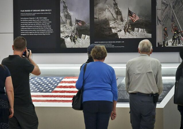 Visitors view the display for the American flag, left, that firefighters hoisted at ground zero in the hours after the 9/11 terror attack  at the Sept. 11 museum in New York