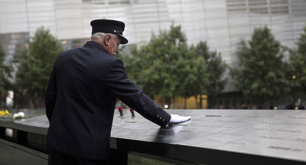 A member of the New York Fire Department places his hand on the memorial before a ceremony marking the 14th anniversary of the 9/11 attacks, at the National September 11 Memorial and Museum in Lower Manhattan in New York