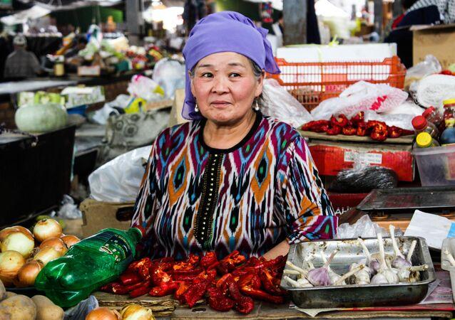 A woman sells vegetables in Osh Bazaar in Bishkek