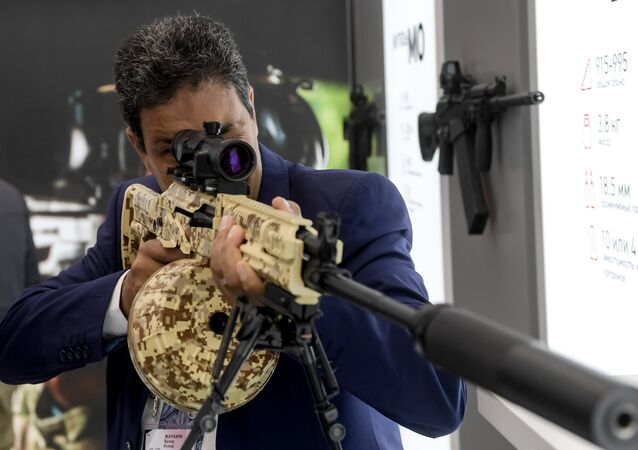 A visitor reviews an RPK-16 light machine rifle at the Kalashnikov pavilion, at the ARMY 2016 International Military Forum, at the exhibition center of the Patriot Military Park of the Russian Armed Forces in the Moscow Region.
