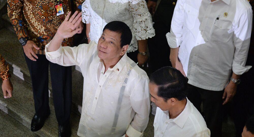 Philippine President Rodrigo Duterte (C) waves next to Indonesian President Joko Widodo (lower R) during a visit to Tanah Abang market in Jakarta
