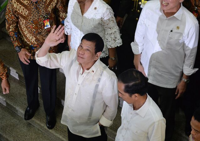 Philippine President Rodrigo Duterte (C) waves next to Indonesian President Joko Widodo (lower R) during a visit to Tanah Abang market in Jakarta