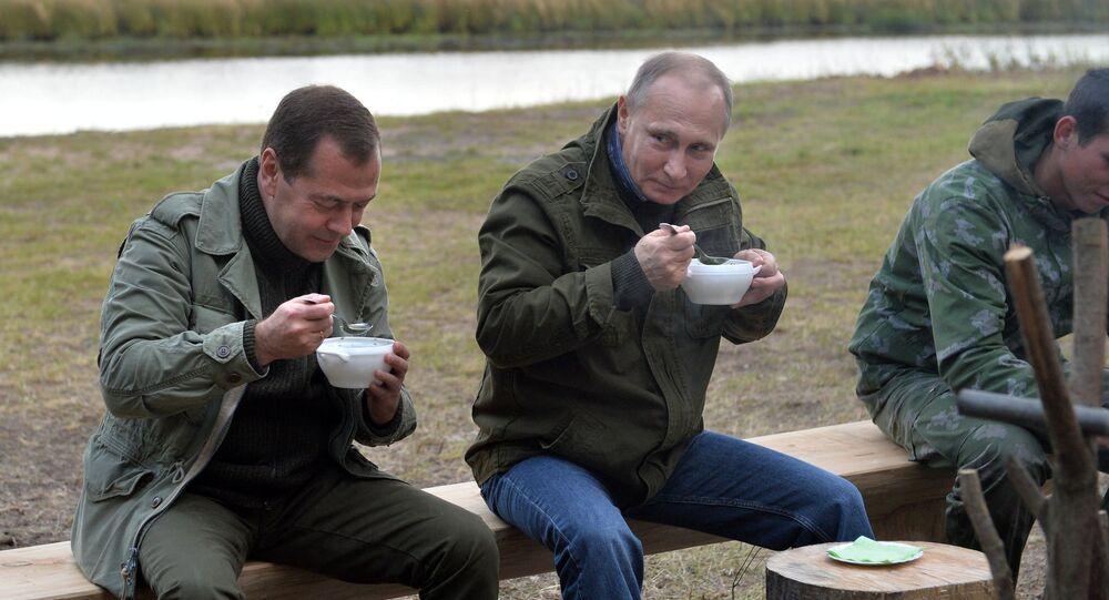 September 10, 2016. Russian President Vladimir Putin, second right, and Prime Minister Dmitry Medvedev, left, have fish soup after a boat trip on Lake Ilmen, Novgorod Region.