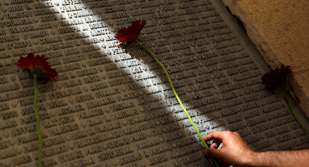 A man lays a flower on a monument engraved with names of victims of the September 11th attacks, during a memorial event marking the 15th anniversary of September 11, 2001 attacks in the U.S., at the 9/11 Living Memorial Plaza in Jerusalem