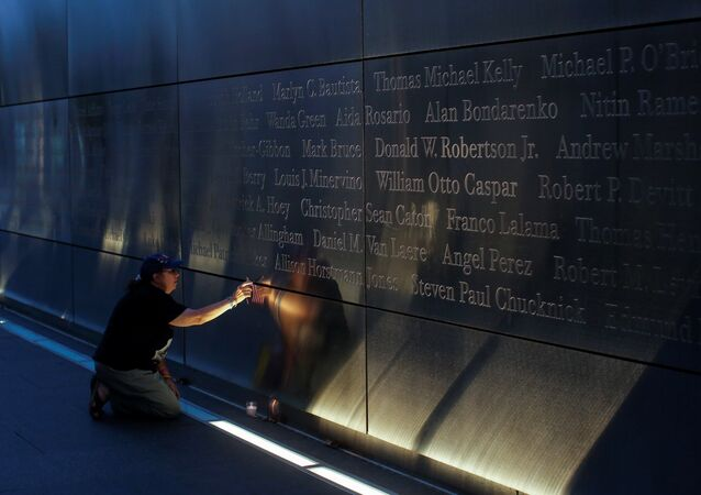 A mourner places a flag in the Empty Sky memorial on the morning of the 15th anniversary of the 9/11 attacks in New Jersey, U.S