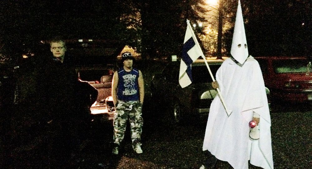 Sept. 24, 2015 photo, a group of demonstrators including one wearing an outfit in the style of the Ku Klux Klan stand in protest against refugees near a former army barracks in Hennala district in Lahti, Finland.