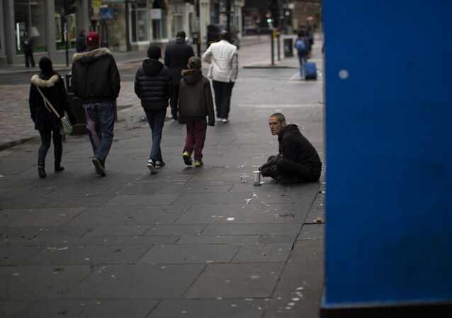 In this Sunday, July 3, 2016 photo, people walk by a beggar at a street in downtown Glasgow, Scotland