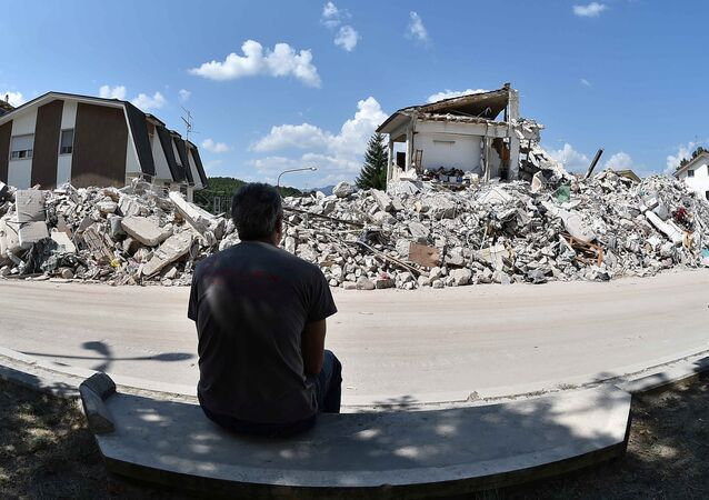 A man sits in front of collapsed houses following the earthquake in Amatrice, central Italy, August 30, 2016
