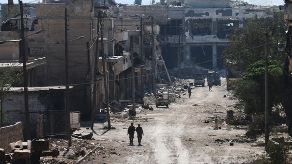 Syrian pro-regime fighters walk in a bombed-out steet in Ramussa on September 9, 2016, after they took control of the strategically important district on the outskirts of the Syrian city of Aleppo yesterday - Sputnik International