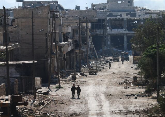 Syrian pro-regime fighters walk in a bombed-out steet in Ramussa on September 9, 2016, after they took control of the strategically important district on the outskirts of the Syrian city of Aleppo yesterday