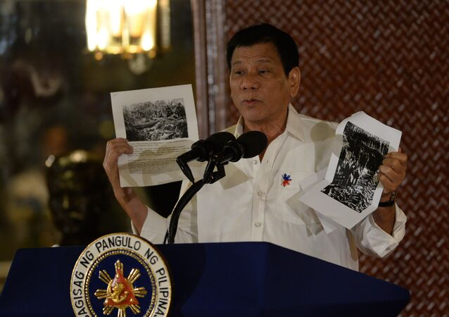 Philippine President Rodrigo Duterte holds up a photo and cites accounts of US troops who killed Muslims during the US's occupation of the Philippines in the early-1900s, during a speech at the Malacanang palace in Manila on September 12, 2016
