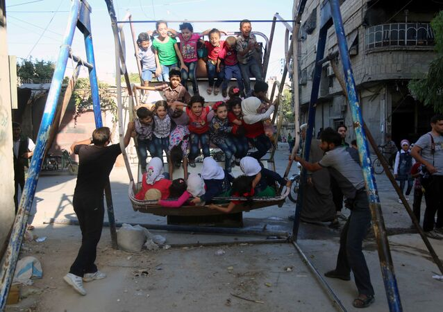 Syrian children ride an attraction in the Syrian rebel-held town of Arbin, in the eastern Ghouta region on the outskirts of the capital Damascus, as they celebrate the Muslim Eid al-Adha holiday on September 13, 2016