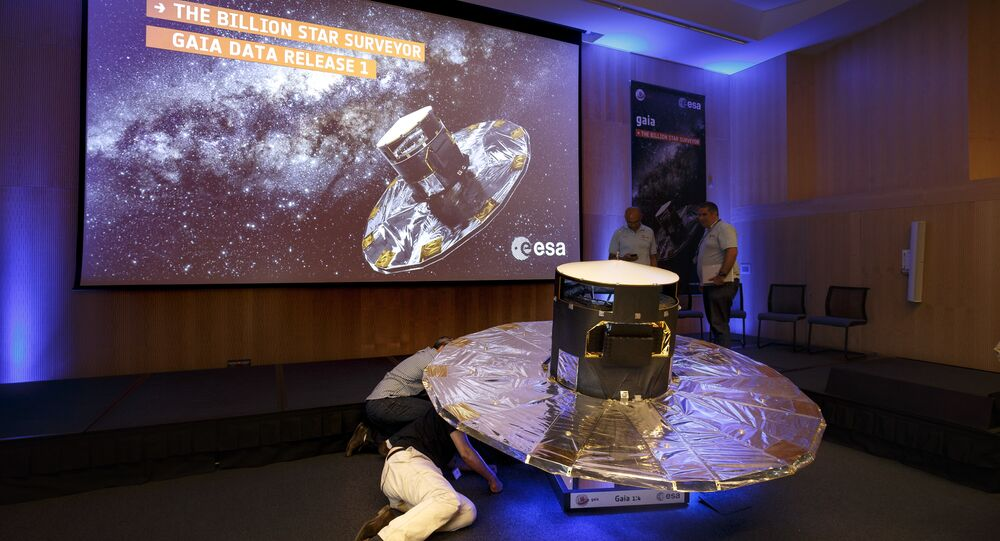 Scientists look under a scaled reproduction of the GAIA surveyor at an event of the European Space Agency, or ESA, to release the first data on its GAIA mission to make a space map, at the ESA center in Villanueva de la Canada, near Madrid, Spain, Wednesday, Sept. 14, 2016